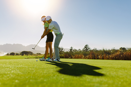 Man teaching woman to play golf while standing on field. Personal trainer giving lesson on golf course. Stock Photo