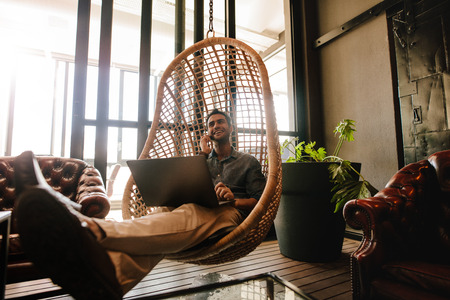 Jonge man zittend op een rieten opknoping stoel in kantoor lounge met laptop en praten op mobiele telefoon. Zakenman ontspannen in office lounge tijdens pauze.