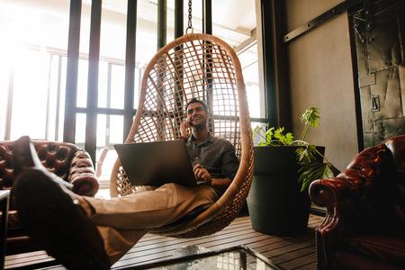 Junger Mann sitzt auf einem Korbweide hängenden Stuhl in Büro-Lounge mit Laptop und reden über Handy. Geschäftsmann Entspannung im Büro Lounge während der Pause. Standard-Bild - 76970903