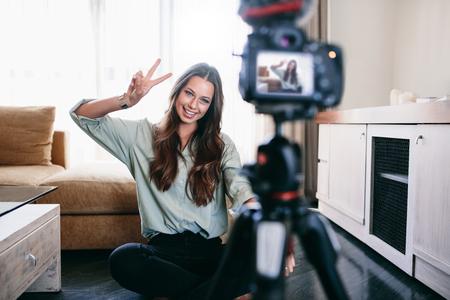Jonge vrouwenvlogger die overwinning of vredesteken toont terwijl het opnemen van haar dagelijkse videoblog. Vlogger gebruikt een camera op een statief om haar video op te nemen.