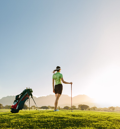 Full length of young woman standing on golf course on a summer day. Rear view of female golfer with golf club on field looking away. Stock Photo