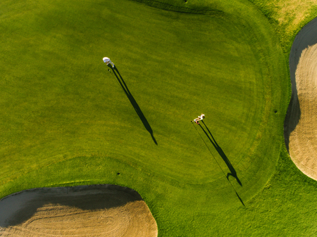 Aerial view of professional golfers playing on putting green on a summer day. Players on a green golf course. Фото со стока