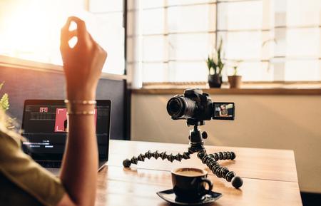 Vrouwelijke vlogger die camera bekijkt terwijl het bewerken van video op haar laptop. Jonge vrouw die aan computer met koffie en camera op haar bureau werkt.