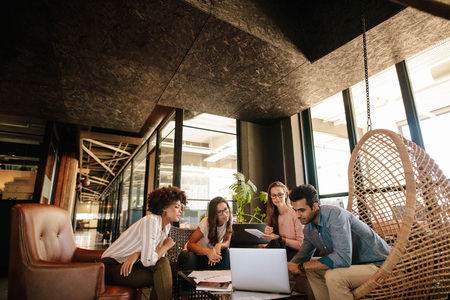 Équipe de création d'entreprise utilisant un ordinateur portable au cours de la réunion. Jeunes hommes d'affaires multiethniques réunion dans les bureaux modernes.