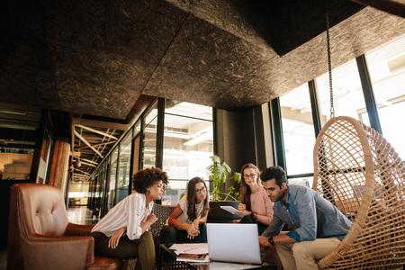 Creatief commercieel team die laptop met behulp van tijdens vergadering. Jong multi etnisch zakenlui die in modern bureau samenkomen.