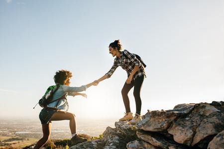 Jonge vrouw helpen vriend om de rots te beklimmen. Twee jonge vrouwtjes wandelen in de natuur. Stockfoto