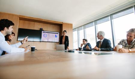 Colleghi di lavoro che lavorano insieme in una sala conferenze. Multi gruppo etnico di uomini d'affari che discutono strategia aziendale.