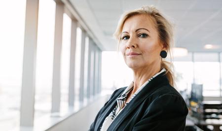 自信を持ってカメラを見て成熟した実業家の肖像画。事務所に立っている美しい白人女性起業家の水平方向ショット。