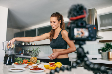 tripod mounted: Young lady in sports wear preparing fruit juice while a tripod mounted camera is recording a video. Woman recording content for her vlog in kitchen.