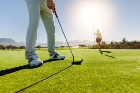 Vista dal basso del golfista sul putting green in procinto di prendere il colpo. Giocatore di golf maschio che mette sul verde con il secondo giocatore femminile nei precedenti che tengono la bandiera. Archivio Fotografico - 77014952