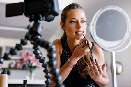 tripod mounted: Young lady applying lip color looking into a mirror while recording her video on a tripod mounted camera. Woman making a video for her blog on cosmetics.
