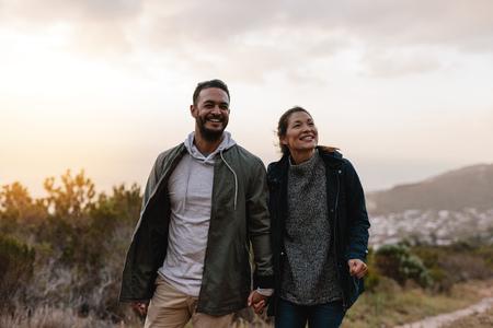 田舎を歩いて幸せなハイカーのカップルの肖像画。若い男と女ハイキングとよそ見。