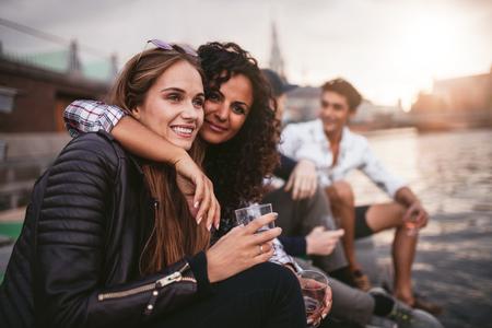 mujeres juntas: Disparo de amigos de mujeres jóvenes divertirse con bebidas en el lago. Grupo de personas que cuelgan en el lago junto.