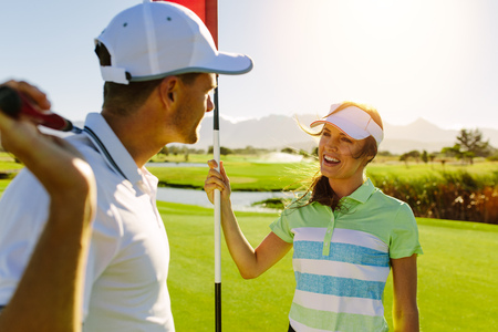 Golfing couple on the putting green at the golf course. Male with golf stick and female holding flag. Stock Photo