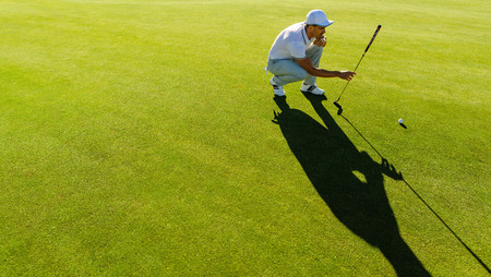 Professional golfer check line for putting golf ball on green grass. Golf player crouching and study the green before putting shot