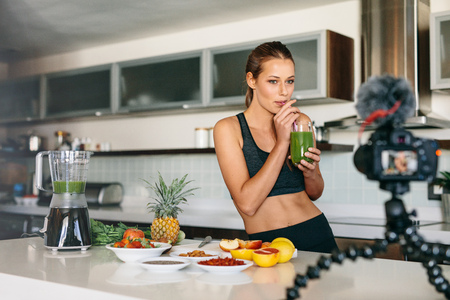 tripod mounted: Young lady drinking green juice at the kitchen table looking at a camera mounted on tripod. Woman preparing a healthy breakfast with fruits and vegetables.