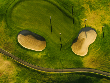 Aerial view of a beautiful golf course with players. Putting green with bunkers. 스톡 콘텐츠