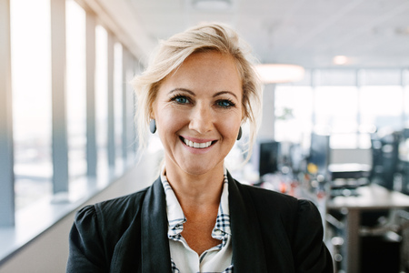 Close up portrait of successful mature businesswoman standing in office. Caucasian female executive in suit looking at camera and smiling. Stock Photo