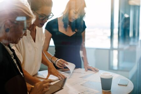 Three female colleagues discussing over documents on table. Team of professionals having a standing meeting around table in office.