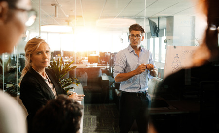 strategy meeting: Mature businessman making a presentation on a flip-chart and discussing. Business team during strategy meeting in modern office.