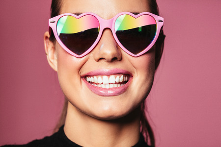 Closeup portrait of beautiful young woman wearing heart shaped sunglasses and smiling against pink background. Stock Photo