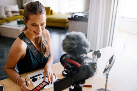 tripod mounted: Woman making a video for her blog on cosmetics. Young lady holding color palette while recording her video on a tripod mounted camera.