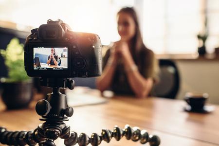 Vrouwelijke vlogger registreert inhoud voor haar videoblog. Jonge vrouw in focus op digitale camera scherm. Stockfoto