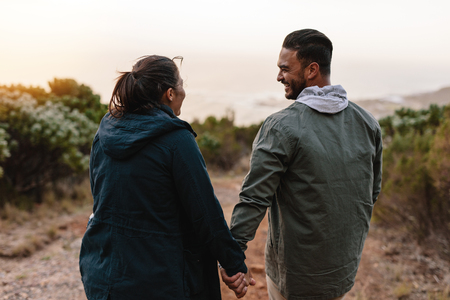 Rear view of young people walking through the country path. Happy young man and woman hiking holding hands and smiling.