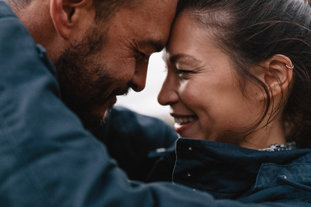 Close-up side portrait of young mixed race couple in love. Romantic couple embracing each other and smiling.