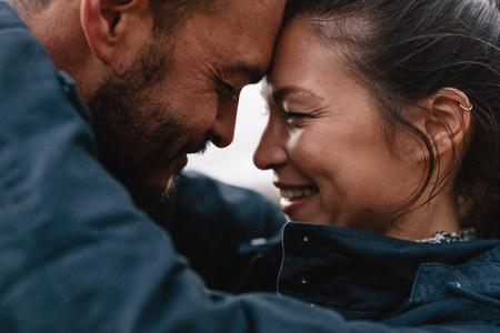Portrait de côté gros plan du couple de jeunes métis amoureux. Couple romantique s'embrassant et souriant.