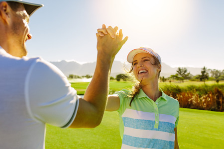 Happy male and female friends giving high-five at golf course after the game. Pro golfer enjoying the game on field and shaking hands. Stock Photo