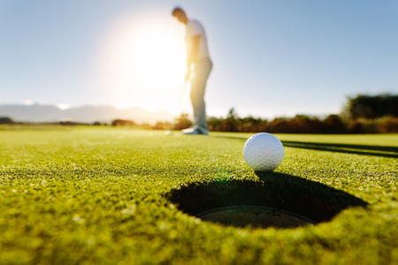 Pro golfer putting golf ball in to the hole. Golf ball by the hole with player in background on a sunny day. Stock Photo