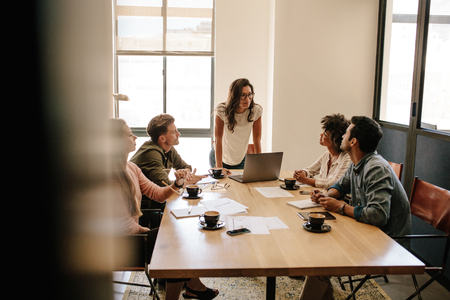 Shot of multi ethnic business people having a meeting in office. Business team sitting around a table with woman giving presentation.