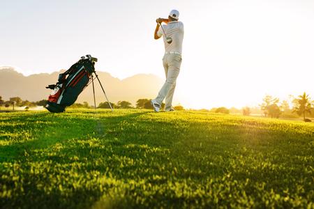 Froschperspektive des Berufsspielers Schuss bei der Stellung auf Feld nehmend. In voller Länge vom schwingenden Golfclub des Golfspielers am sonnigen Tag. Standard-Bild