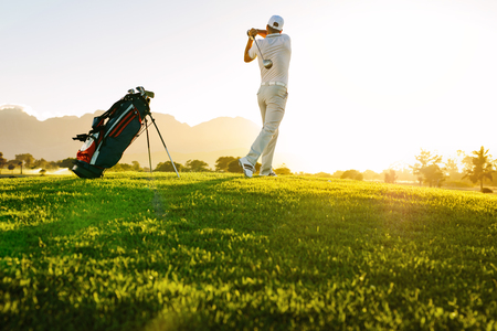 Low angle shot of professional golfer taking shot while standing on field. Full length of golf player swinging golf club on sunny day. Фото со стока