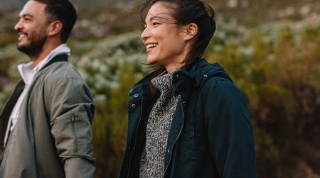 美しいアジアの女性は、田舎の彼氏と歩いています。田舎でカップルのハイキングを笑っています。 写真素材