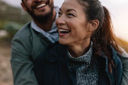 Glimlachende Aziatische vrouw die door haar vriend erachter wordt omhelst van. Paar dat op vakantie geniet van.