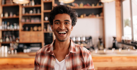 Portrait of happy young man laughing in a cafe. Young african male in a coffee shop having fun.