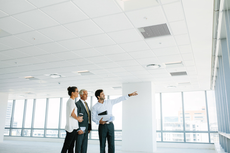 Real estate broker showing office space to clients. Business people and real estate agent at empty office space, with estate broker pointing at something interesting.