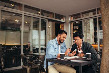 Twee jonge mannen die samen bij koffiewinkel zitten die mobiele telefoon met behulp van. Vrienden die bij koffie en het gebruiken van slimme telefoon samenkomen. Stockfoto