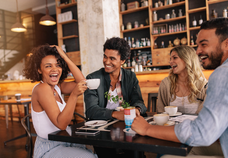 Happy young people sitting around cafe table and drinking coffee. Multiracial group of friends enjoying coffee together in a restaurant. Stock Photo