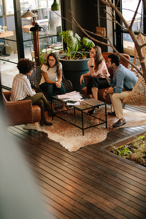 Vertical shot of corporate professionals discussing new ideas in office lobby. Creative business team meeting in office.