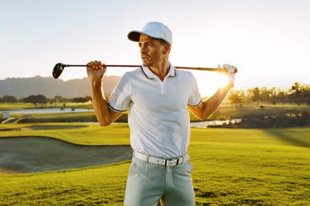 Schot van mannelijke golfspeler met golfclub op cursus. Jonge man met een golfclub en wegkijken op een zonnige dag. Stockfoto