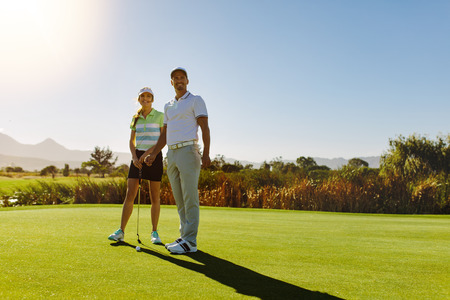 Young couple on putting green at golf course. Male and female golfers at field on sunny day. Stock Photo
