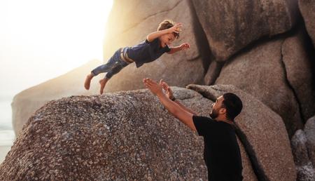 Ontsproten van leuke kleine jongen die in zijn vaderswapens van een grote rots springt. Vader en zoon die van de zomervakantie genieten bij het strand.