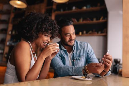 アフリカの女性は彼女のボーイ フレンドの携帯電話で何かを示すのコーヒーを飲んでいます。スマート フォンを見てコーヒー ショップで若いカッ