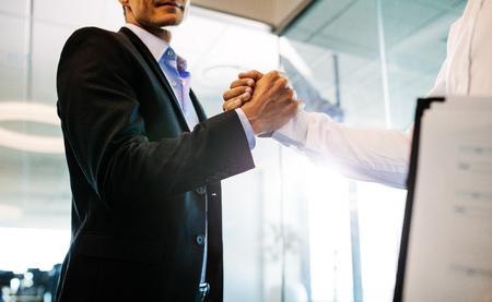 2 実業家のオフィスで震える手。巧妙な取り引きの後ハンドシェイクのクローズ アップ。 写真素材