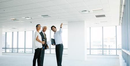 Mannelijke makelaar in onroerend goed die nieuwe bureauruimte toont aan cliënten. Bedrijfsmensen die en nieuw kantoor bespreken bespreken met landgoedmakelaar.