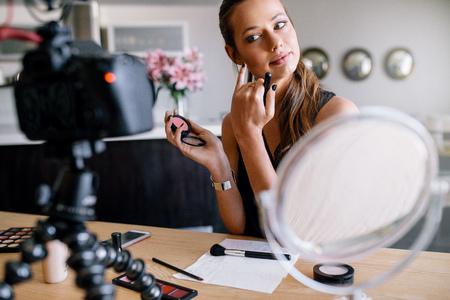 Modeblogger die video opneemt voor haar blog over cosmetica. Jonge vrouw die make-up toepast die een camera onderzoekt die op driepoot wordt bevestigd.