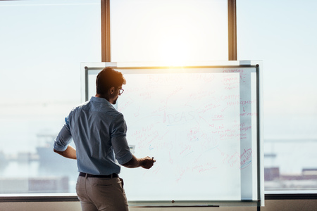 Businessman using whiteboard to present ideas for business decision making. Entrepreneur making a business presentation in office. Stock Photo